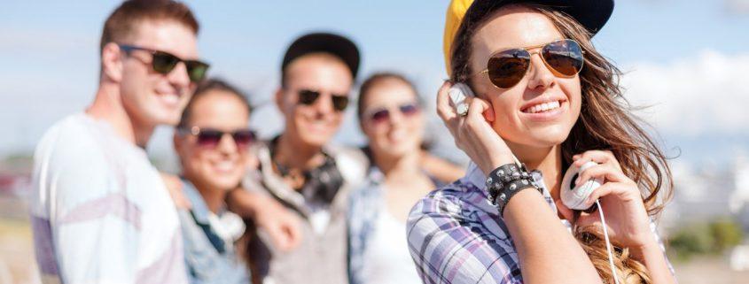 Mädchen mit Kopfhörern und Freunden