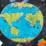 Menschen sitzen um eine Weltkarte herum